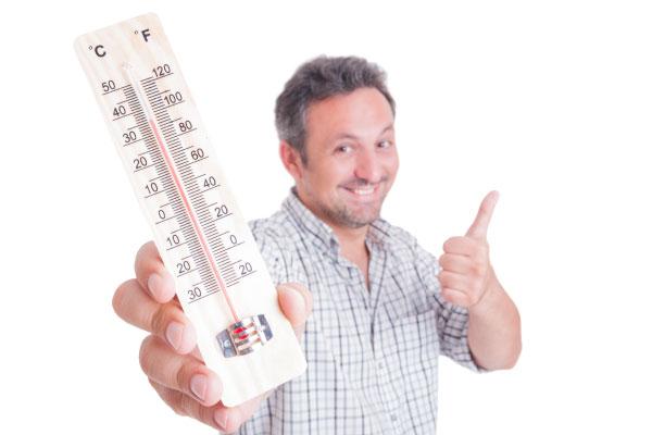 Medelåldersman med stor termometer i handen