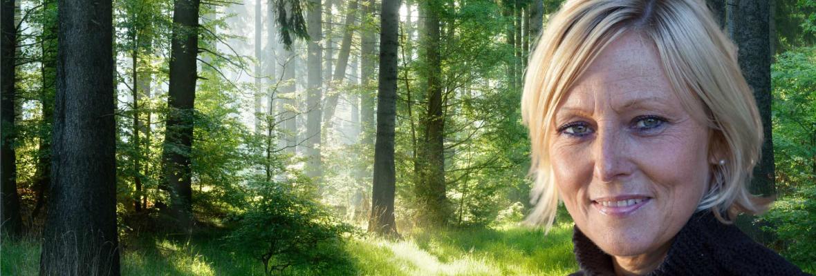 Glad kvinna mot bakgrund av svensk skog